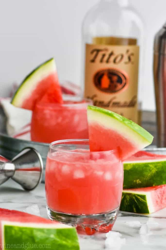 small tumbler of watermelon vodka tonic cocktail with bottle of titos in the background
