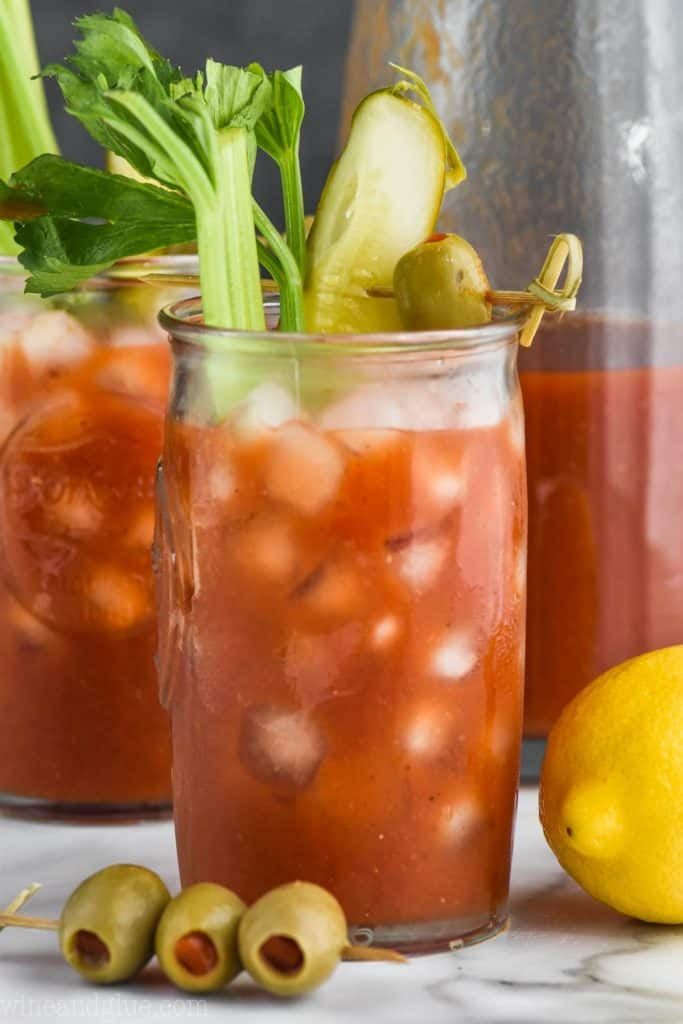 a glass of bloody mary mix recipe garnished with celery, pickle, and olives