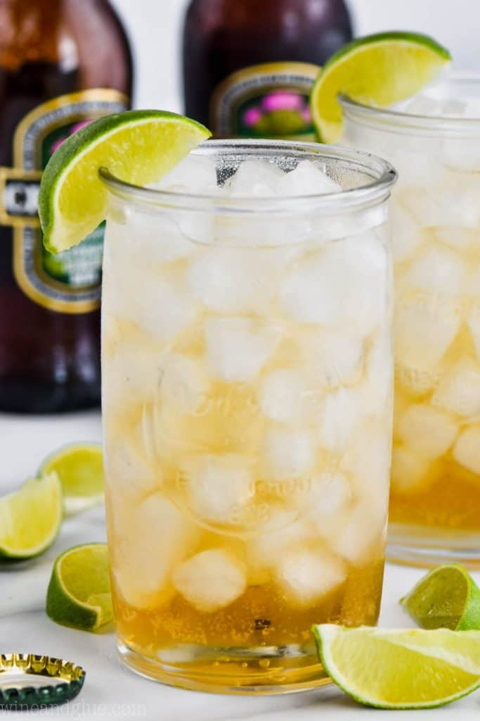 tall glass filled with ice and dark and stormy drink recipe, garnished with a lime wedge