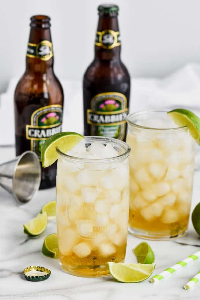 two tall glasses filled with ice and dark and stormy drink recipe, both garnished with lime wedges, and two bottles of ginger beer in the background