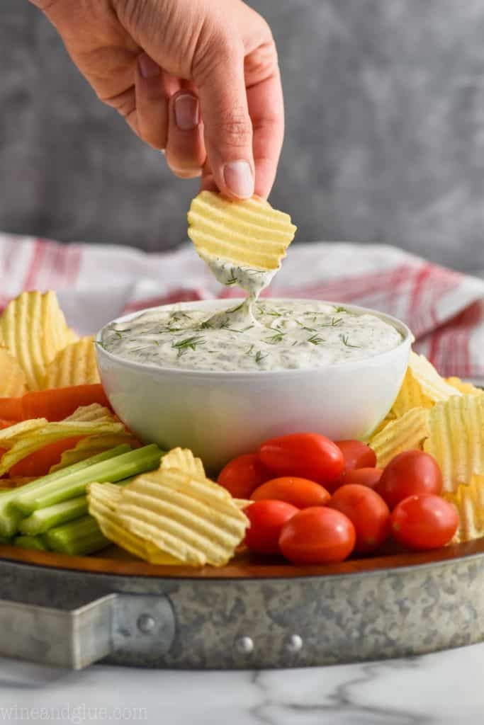 dipping into dill dip with potato chip