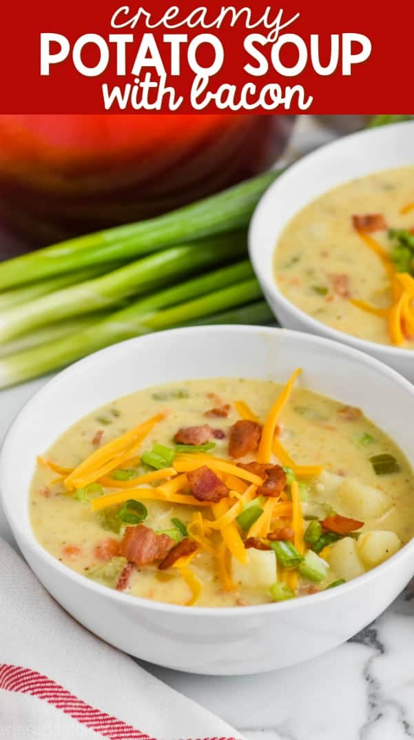 bowl of creamy potato soup with bacon topped with cheese, bacon, and scallions