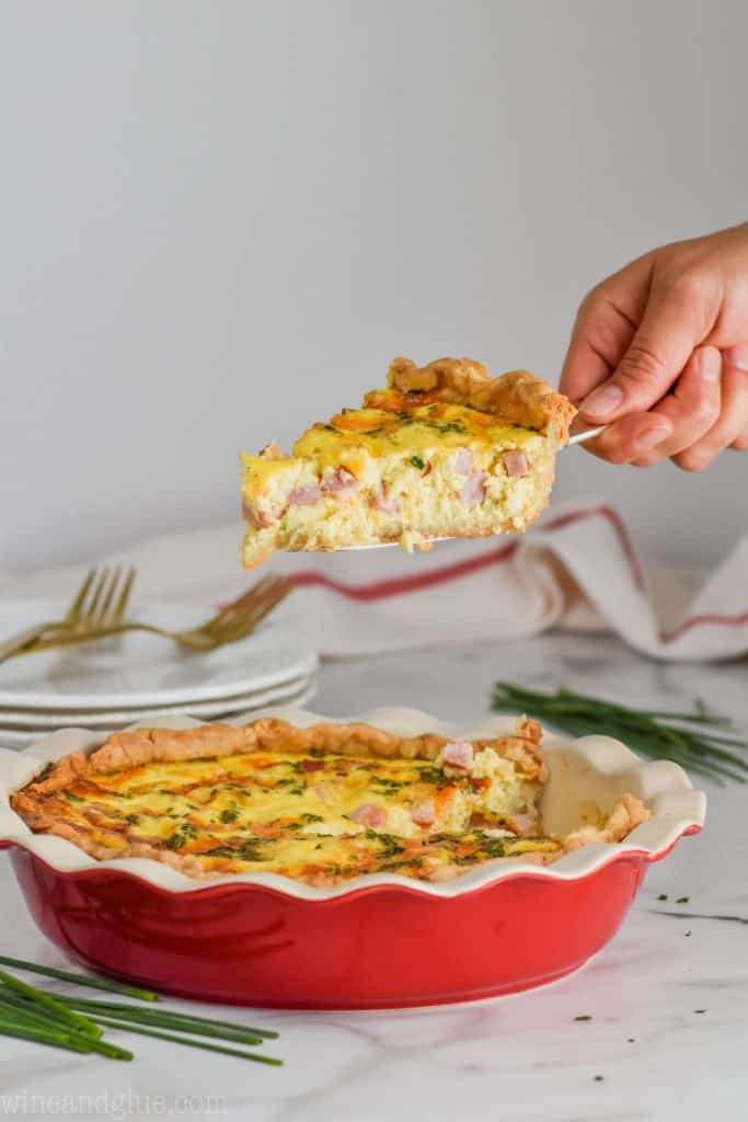 holding a piece of quiche over a pie plate