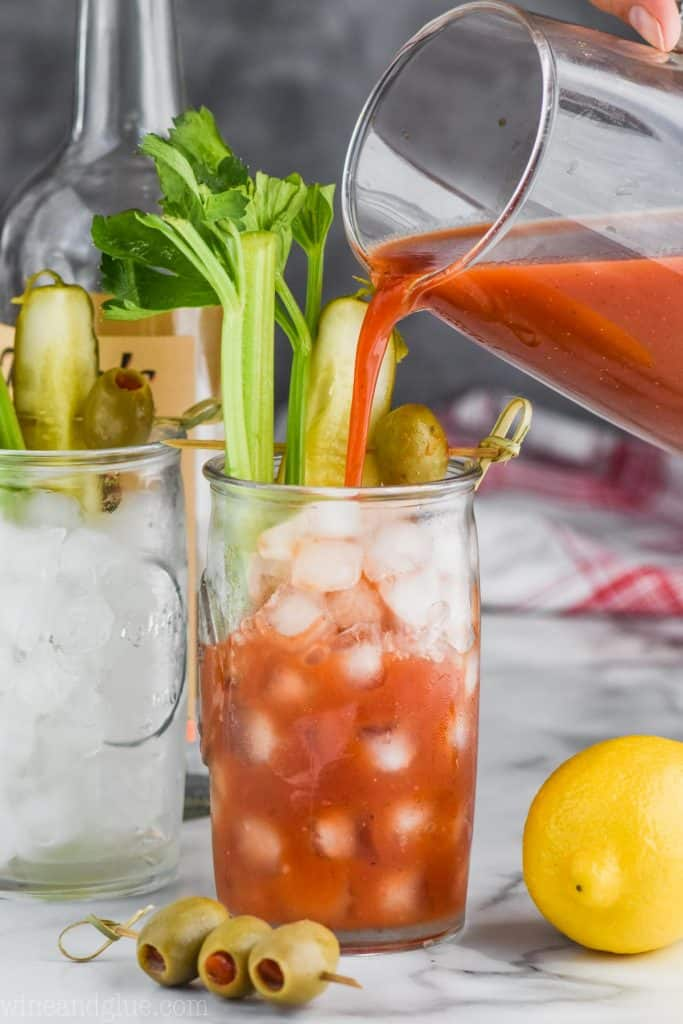 pouring homemade bloody mary mix into a glass of ice thats garnished