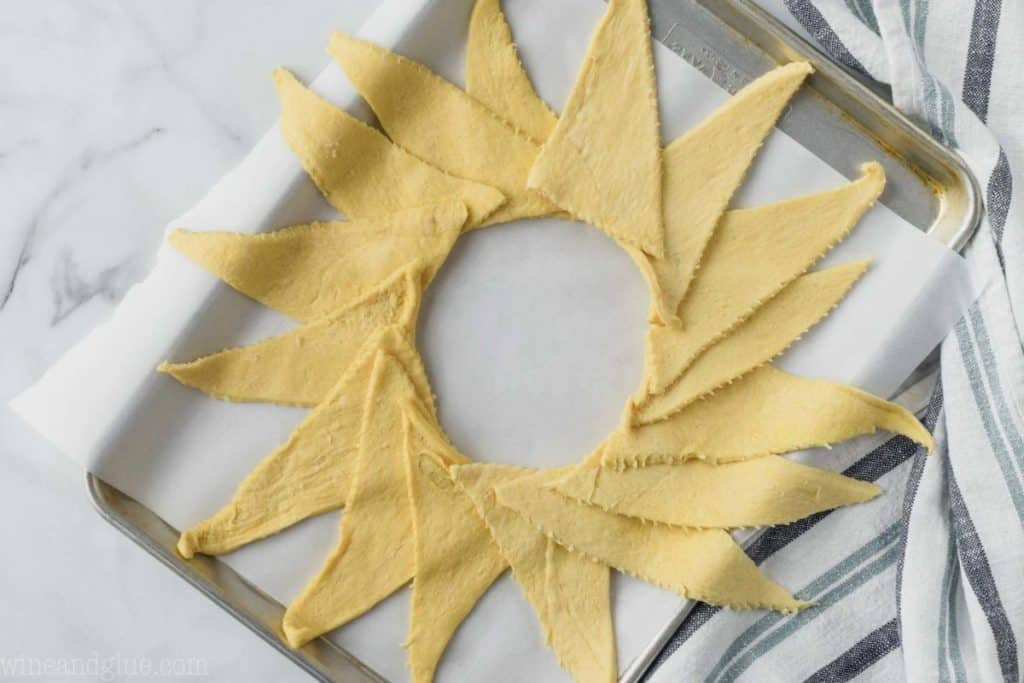 crescent roll dough set out on a baking sheet in a ring with the tips of the triangle facing outside