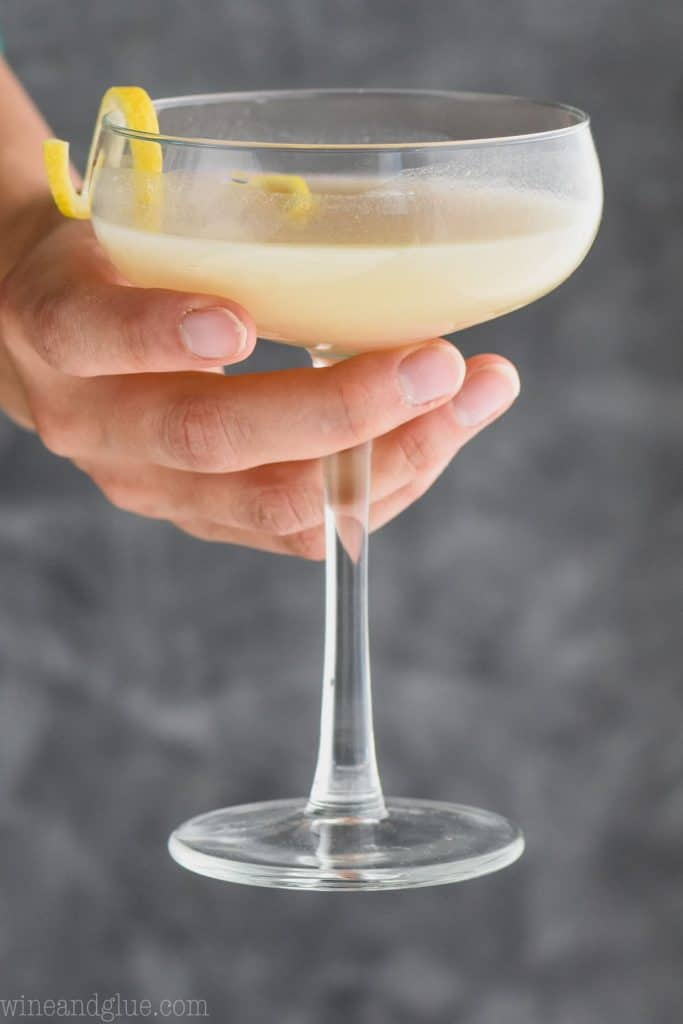 woman holding a glass full of saketini recipe