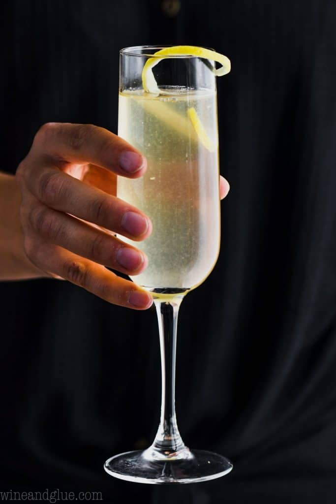up close of a woman holding a champagne flute filled with french 75 cocktail in front of a dark black shirt
