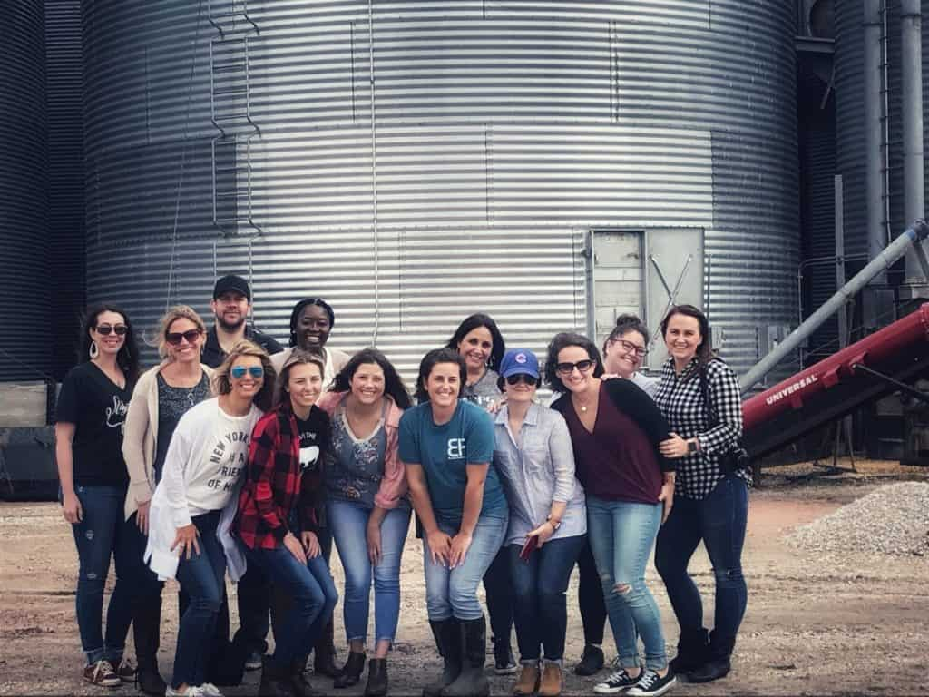 A photo of a group of people in front of a corn silo