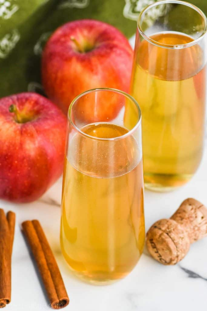 champagne pouring into a glass of bellini drink recipe