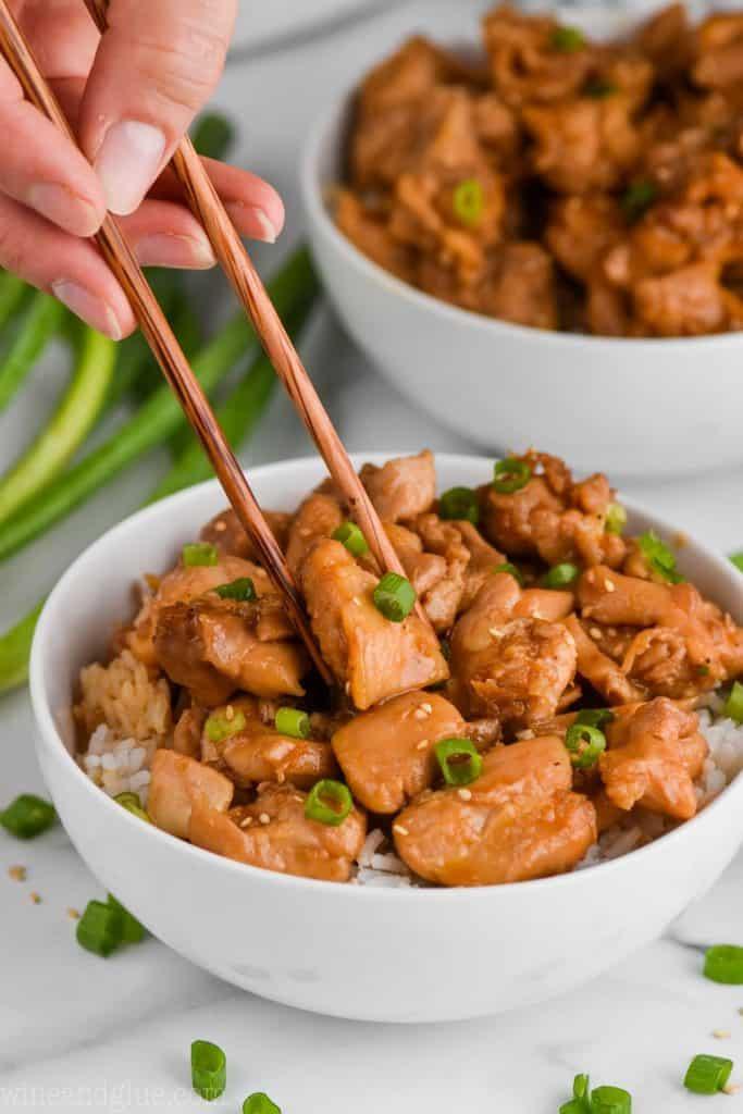 chopsticks picking up a piece of bourbon chicken like food court