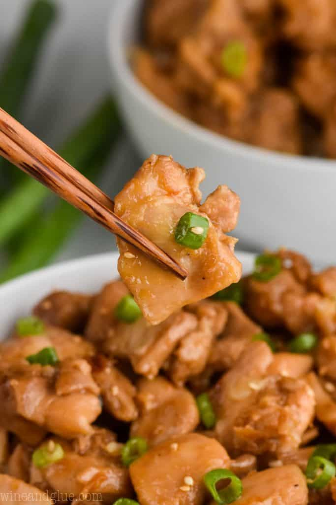 chopsticks holding a piece of the best bourbon chicken