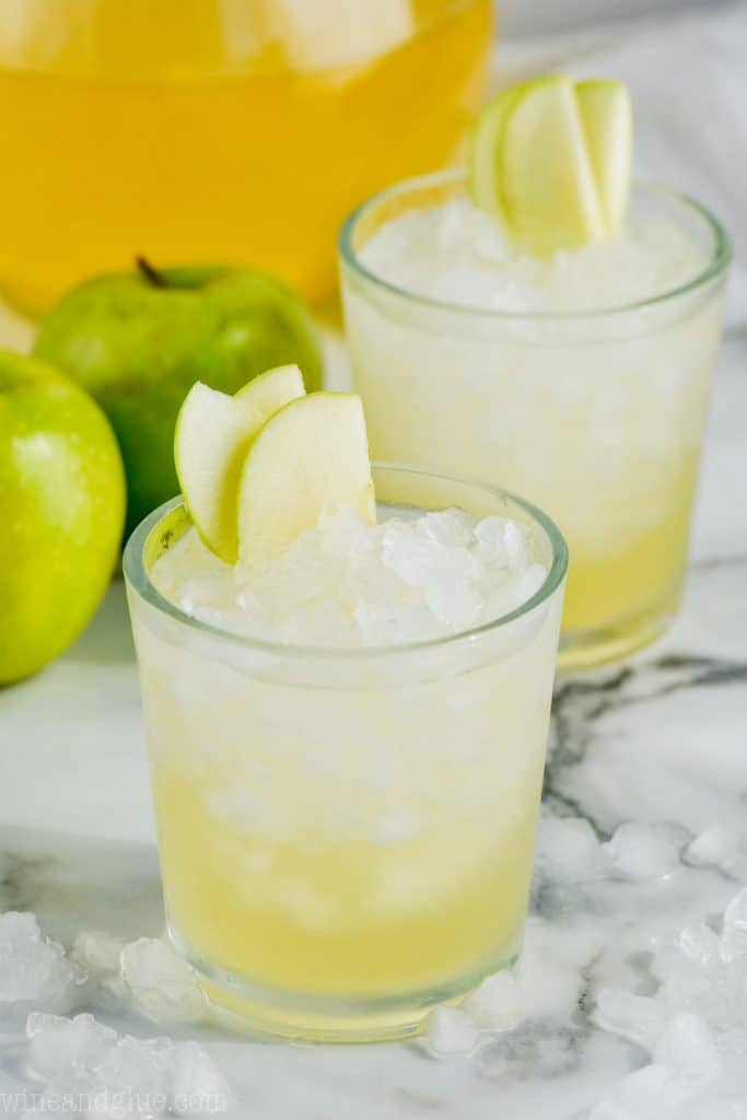two cups of caramel apple vodka punch garnished with sliced apples