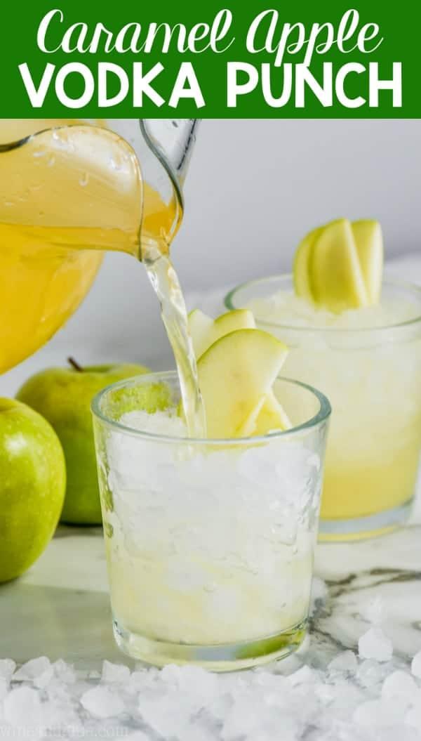 cup of caramel apple vodka punch garnished with sliced apples