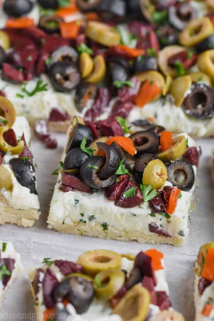 piece of olive pizza amongst the rest of the pieces with black, green, and kalamata olives