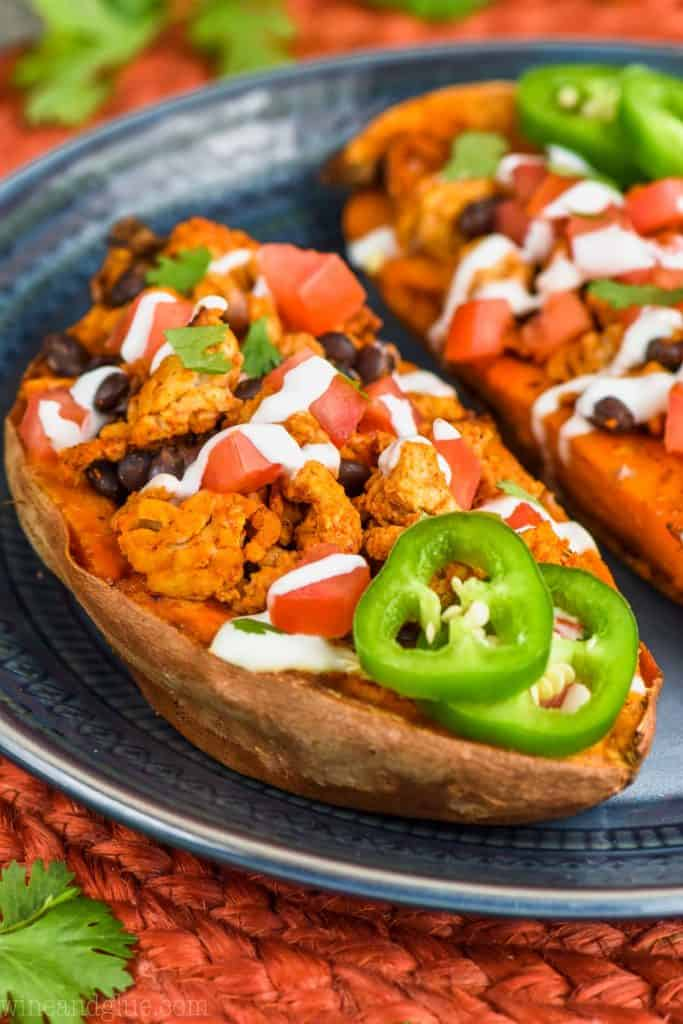 stuffed sweet potatoes garnished with taco fixings on a plate