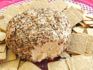 In a middle of plate surrounded by crackers, Aunt Louise's Cheese ball has a small cut out portion.