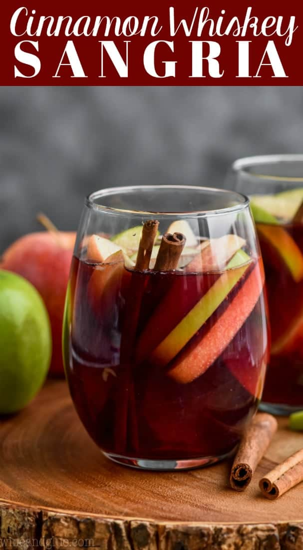 glass of cinnamon whiskey sangria filled with apple slices and cinnamon sticks