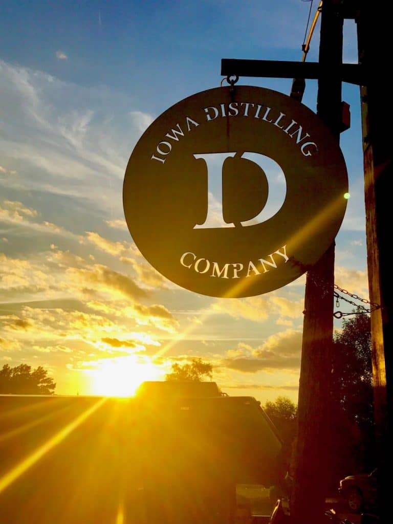 the metal sign hanging outside of the Iowa Distilling Company