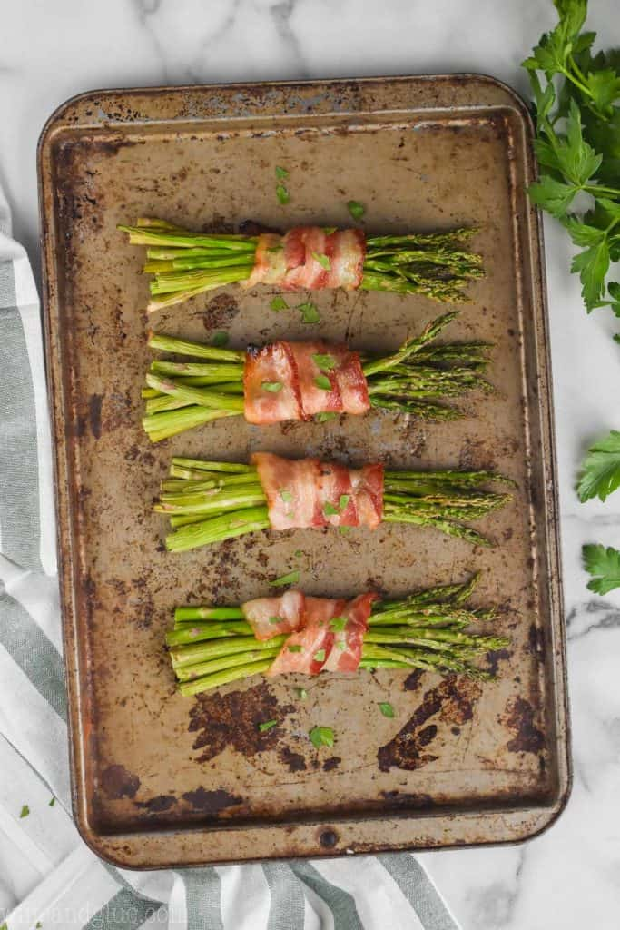 asparagus wrapped in bacon on a baking sheet, fresh from the oven