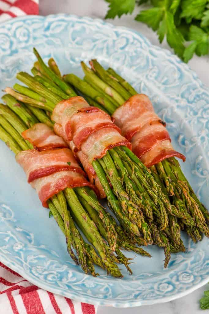 baked bacon wrapped asparagus, a great side dish on a blue platter