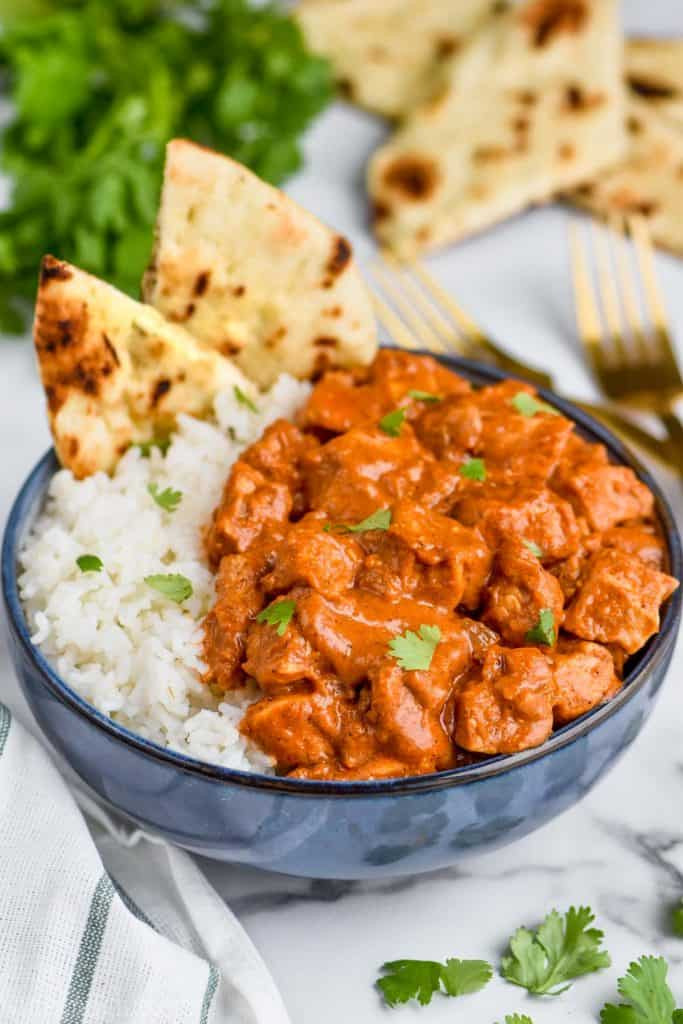 chicken butter masala recipe in a bowl with rice and naan