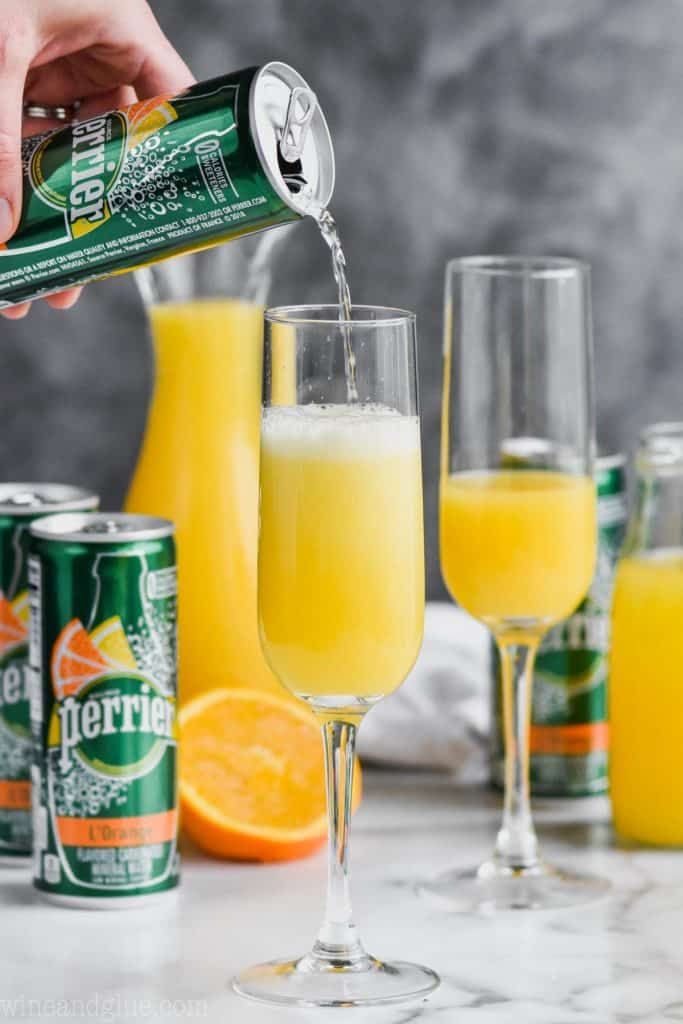 perrier slim being poured into a champagne glass filled with orange juice