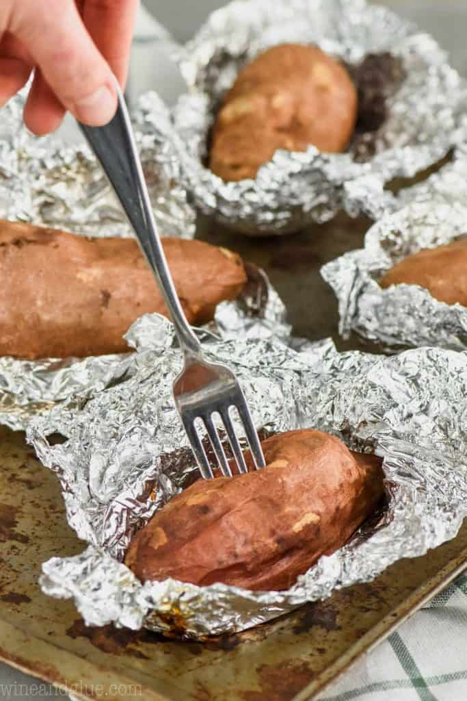 a sweet potato cooked in a crock pot sitting on foil with a fork going in it to check the tenderness