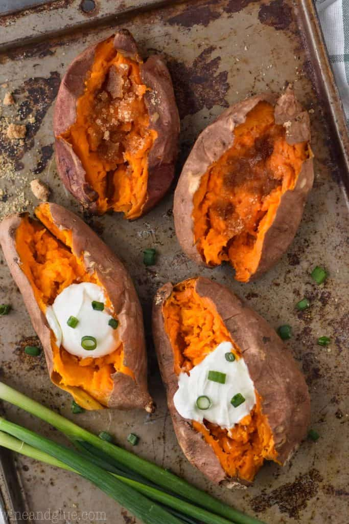 overhead of four sweet potatoes on a baking sheet that have been cooked in a slow cooker
