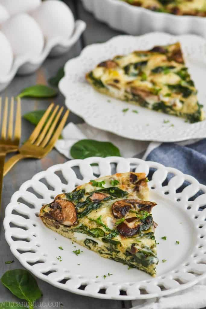 pice of crustless spinach quiche on a white plate with another piece in the background
