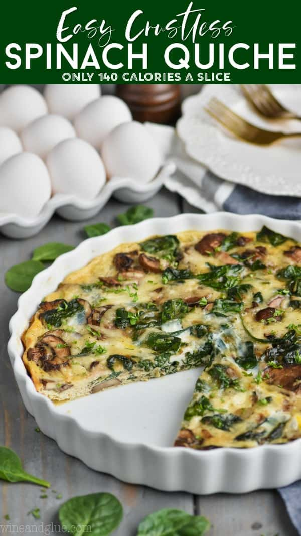 a spinach and mushroom quiche in a white quiche dish with a piece missing