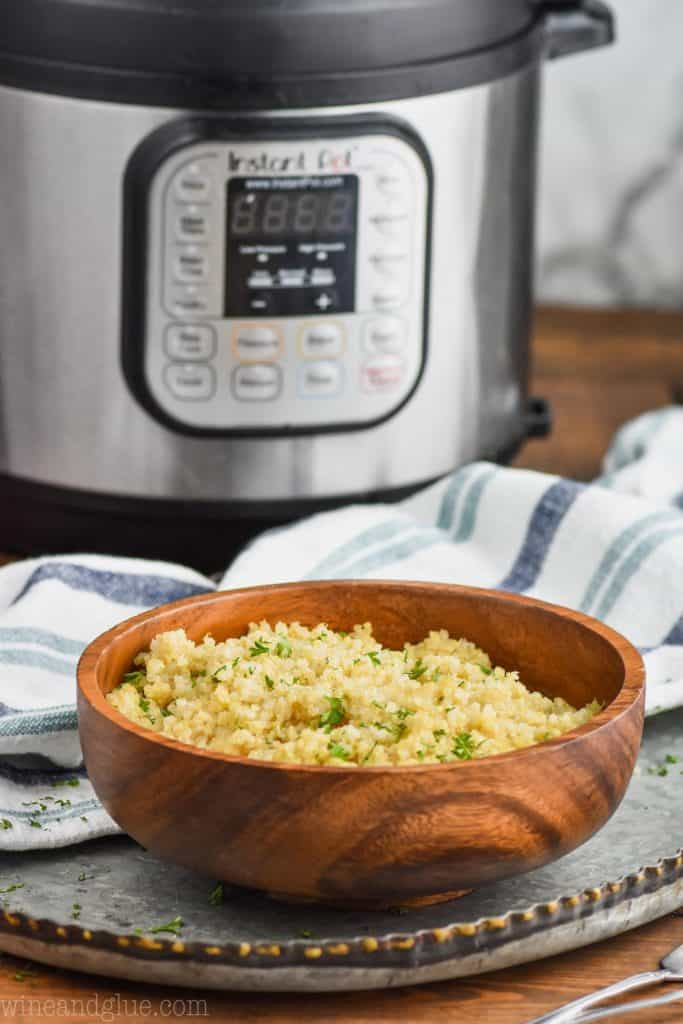small wooden bowl of quinoa in front of an instant pot