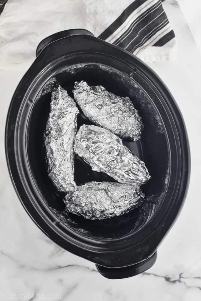 four sweet potatoes wrapped in aluminum foil in the base of a slow cooker