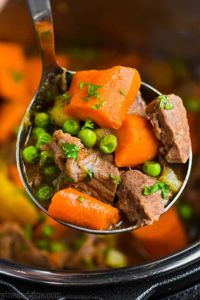 close of up of a ladle holding instant pot beef stew