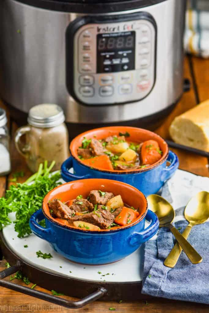 two bowls of instant pot beef stew with pressure cooker in background