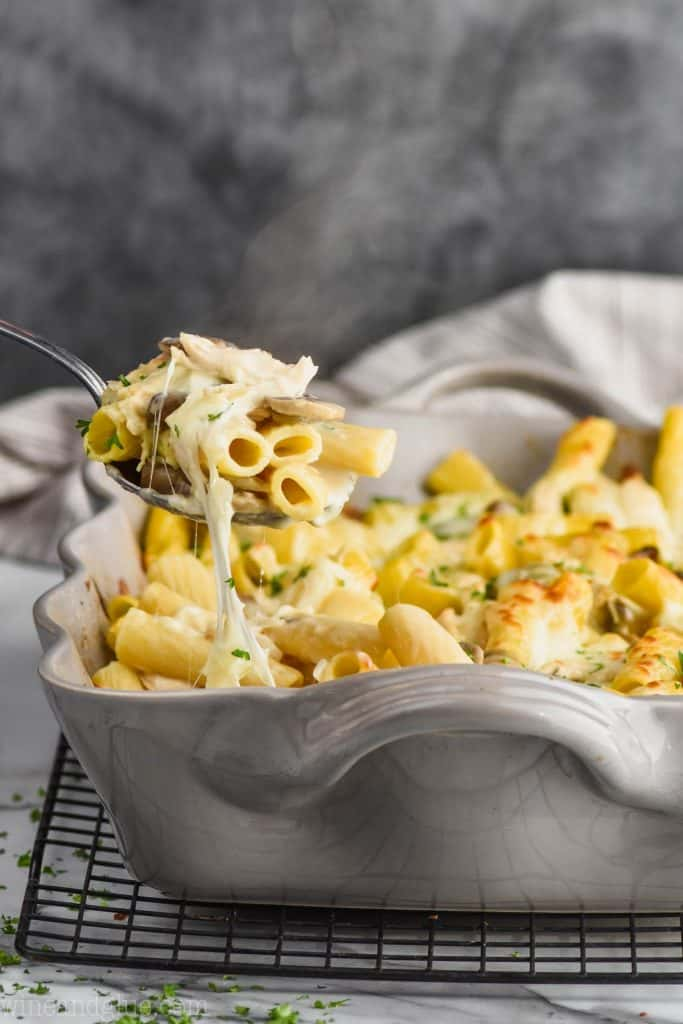 cheesy chicken noodle casserole being pulled out of casserole dish