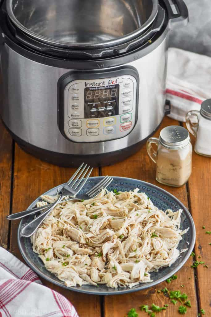instant pot shredded chicken on a plate in front of a pressure cooker