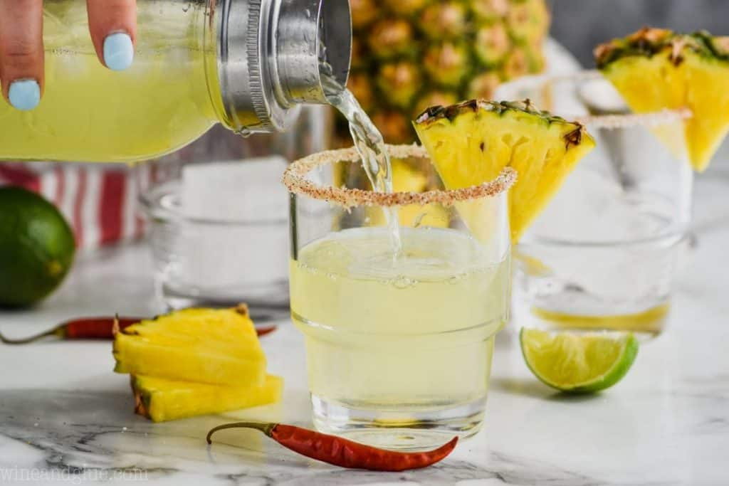 hand pouring spicy pineapple margarita into rimmed glasses