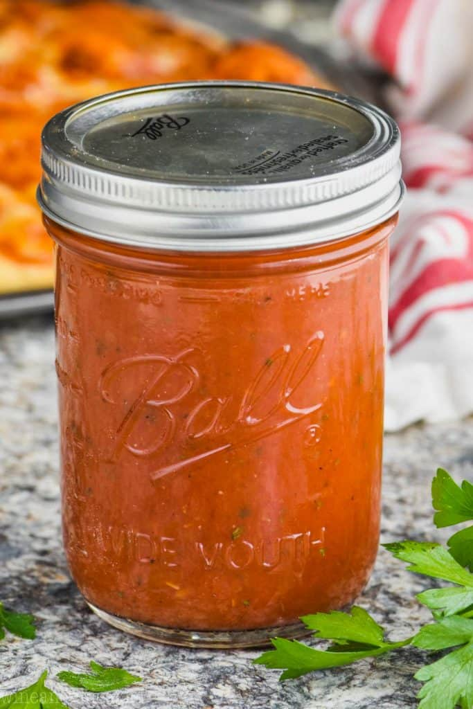 ball jar filled with homemade pizza sauce recipe surrounded by parsley leaves with pizza in the background