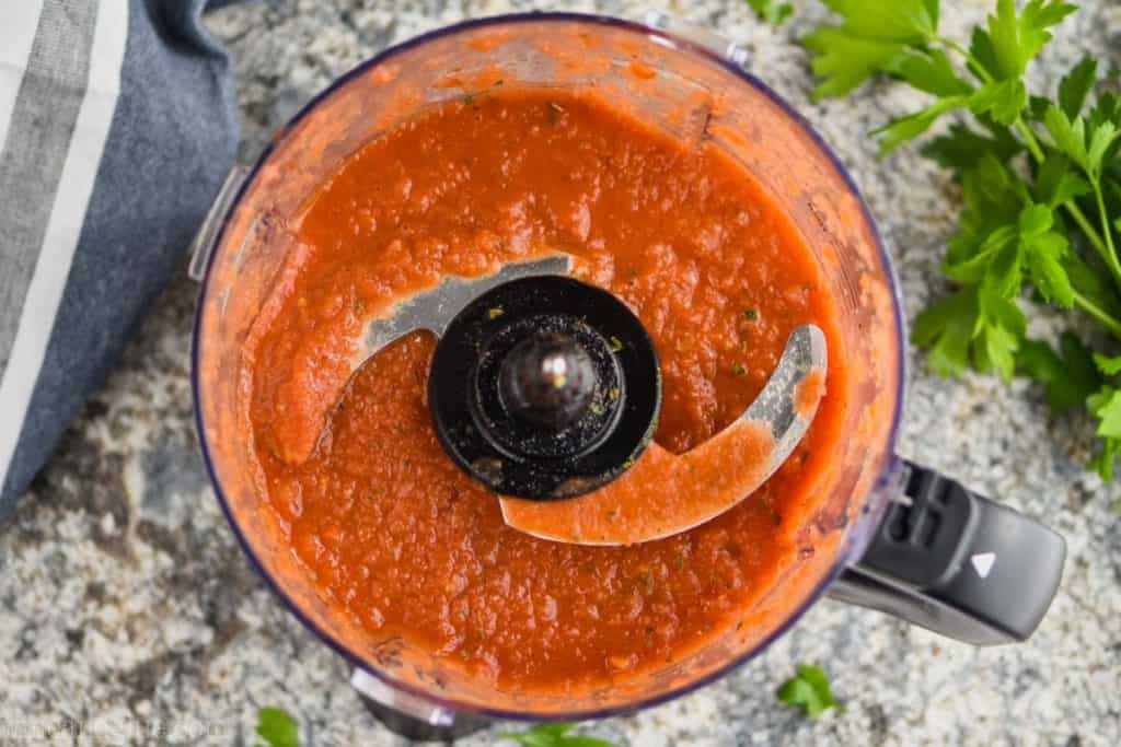 over head view of a food processor filled with pizza sauce from scratch