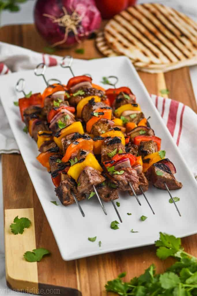 side view of steak kabobs on a white plate