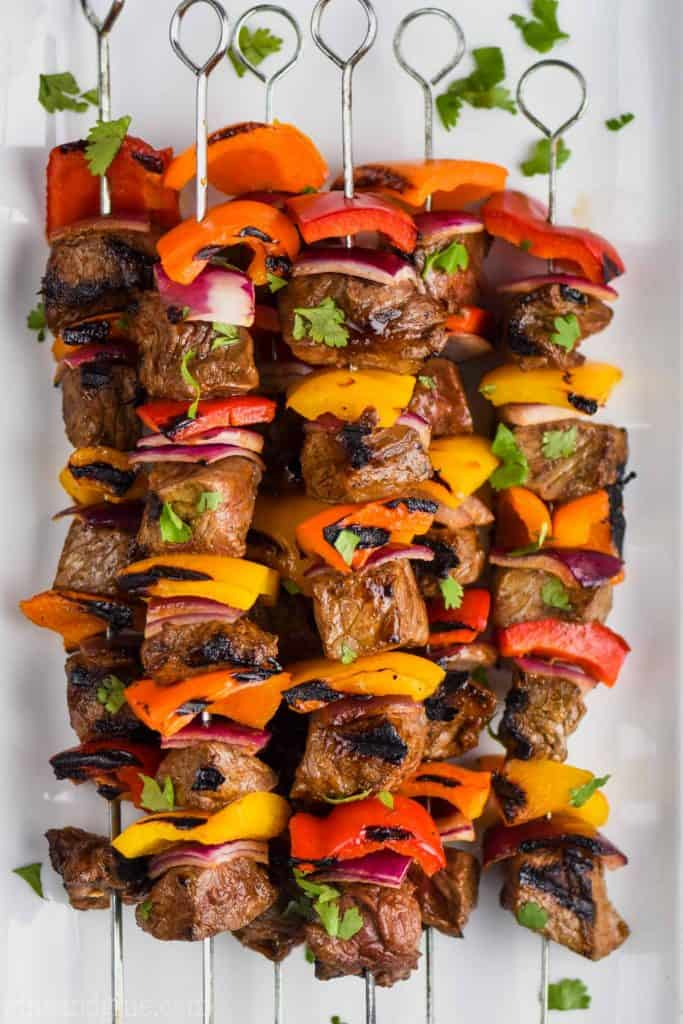 steak kabobs, skewered with metal skewers and flavored with fajita seasoning, on a white plate
