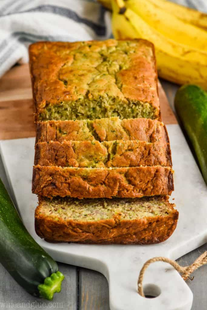 front view of zucchini banana bread recipe sliced on a marble and wood cutting board surrounded by two zucchini and a bunch of bananas on a gray wood board