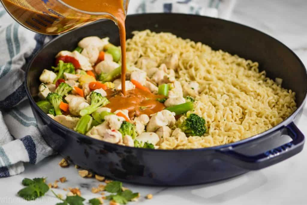 pouring peanut sauce into a skillet that contains vegetables and noodles