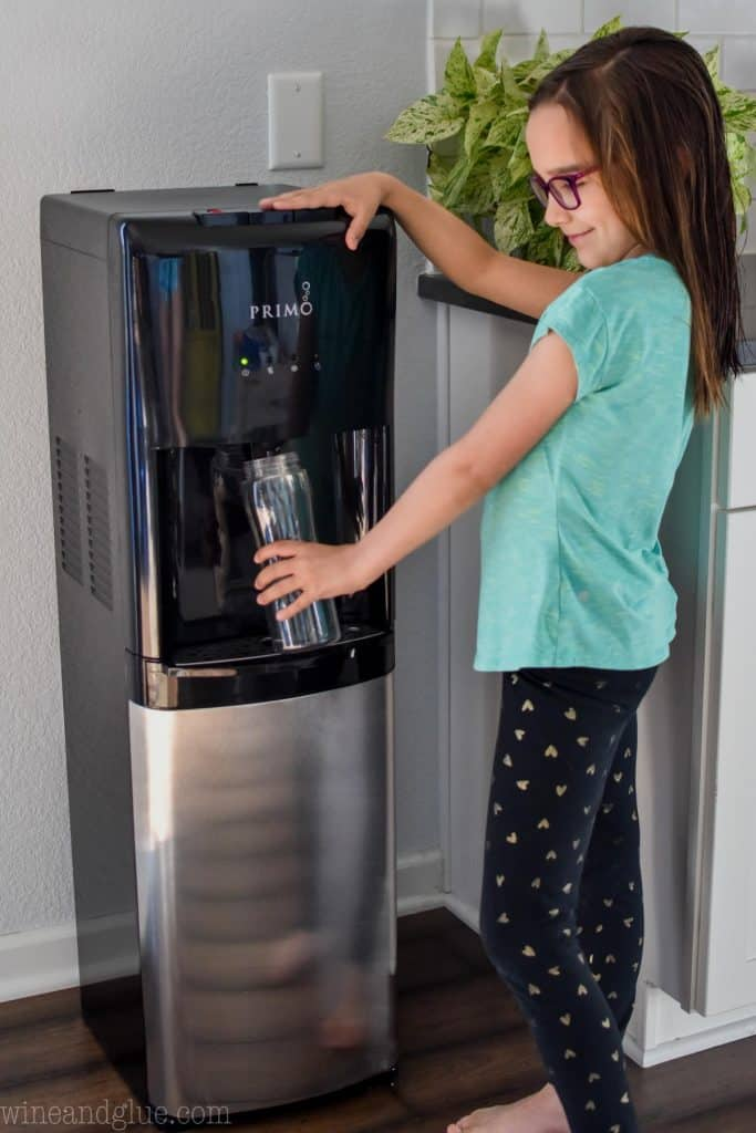 little girl filling water bottle with Primo Water System