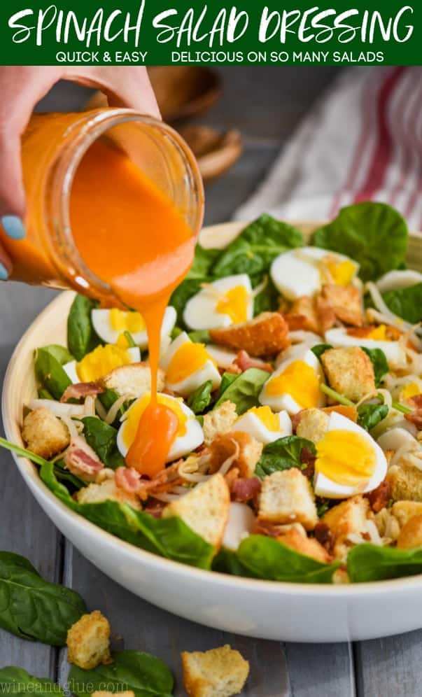 woman pouring red spinach salad dressing on a salad bowl filled with spinach, hard boiled eggs, and croutons