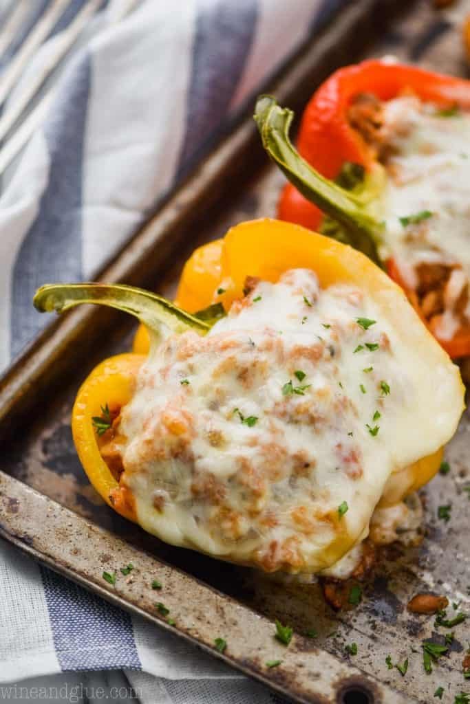 ground turkey stuffed bell pepper with melted cheese and fresh parsley on a baking tray on top of a blue and white striped napkin