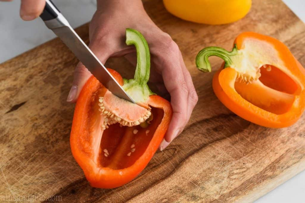 woman cutting the seeds out of the inside of a stuffed pepper