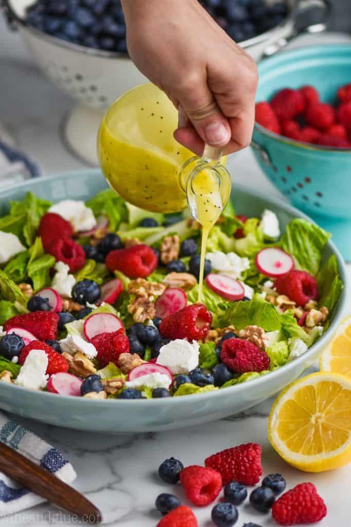 woman pouring lemon vinaigrette salad dressing over a summer salad recipe
