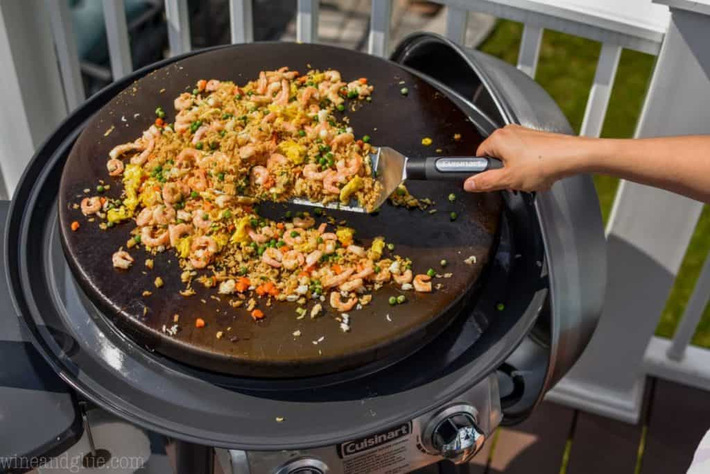 hand holding spatula and dishing up shrimp fried rice recipe off a griddle.