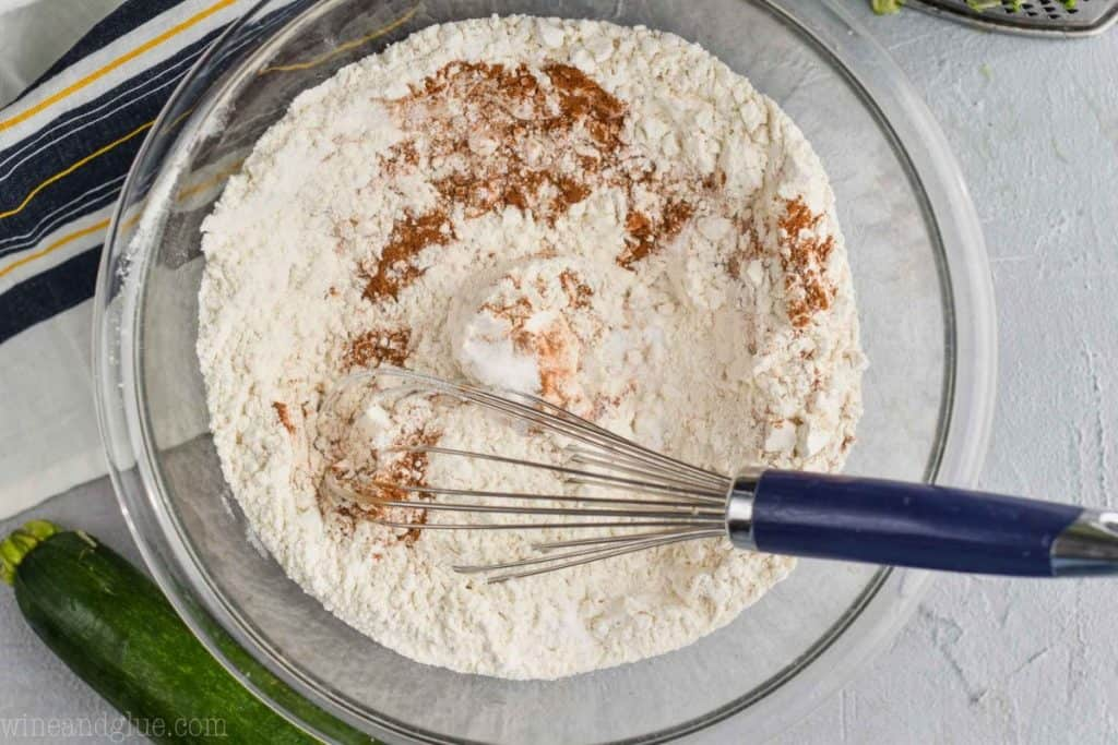 flour, baking soda, salt, and cinnamon being whisked together in a clear glass bowl to make zucchini muffins
